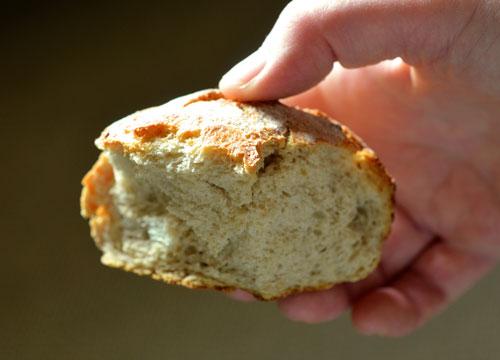 Un hombre sujeta un pedazo de pan listo para comer