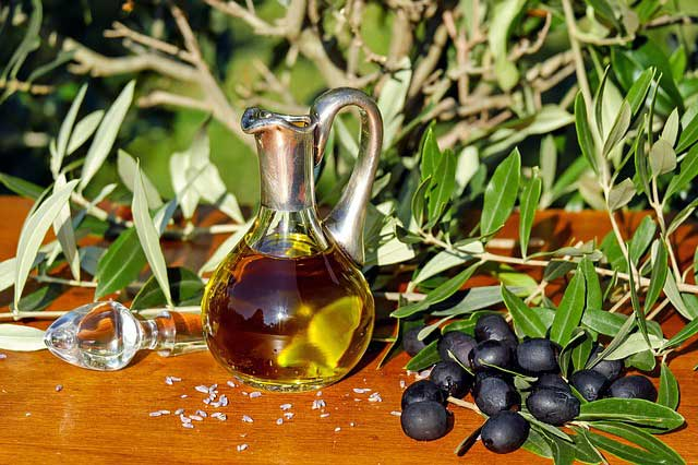 Aceita de oliva en una aceitera rodeada por aceitunas y hojas de olivo